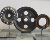 Trio of free-standing industrial gear forms as sculpture or bookend or coffee table piece