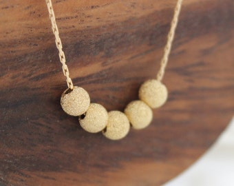 Gold Stardust Necklace   Stardust gold beads on a necklace   Gold jewelry