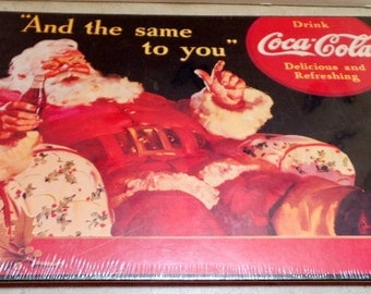 Coke Coca Cola Cardboard store sign, dated 1991.  It depicts the famous Coke Santa, relaxing with an ice cold coke