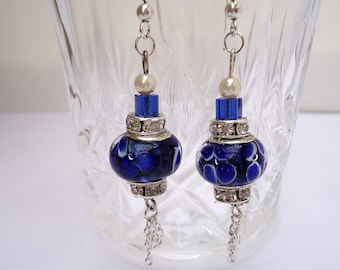 Dangling lampwork earrings in shades of blue.