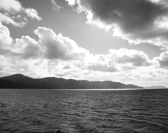 Black and white photography dark sea with dramatic clouds & island silhouette, bright sand, bold ready-to-frame print, interesting decor