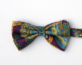 Bow tie handmade pre tied Taklia paisley patterned blue and yellow on a purple background