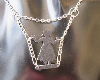 Reversible silhouette girl standing on a swing shrink plastic necklace