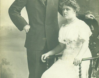 A Proud Man And His Wife Sitting in White Dress Portrait RPPC Real Photo Postcard  Antique Vintage Black and White Photo Photograph