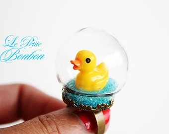Traveling duck in a glass globe ring