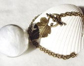 Glass orb necklace, glass orb necklace encases fluffy white feathers with bronze chain and accents