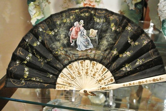 French Silk Fan Hand Painted Black Silk Fan Celluloid Carved Gold Floral Handle Lovers Garden Scene Circa 1940s Made In France Work of Art