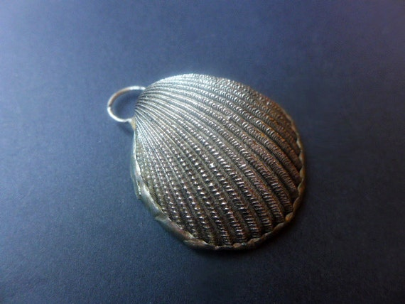 Shell pendant ornament with solder in silver color.