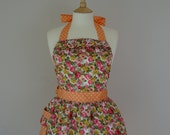 Retro apron with ruffles, vintage style pink and yellow floral pattern on a white fabric.