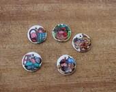 Medallitas en cadena de metal con dibujos de los personajes del cuento de caperucita roja.