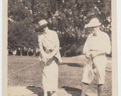 Vintage/Antique beautiful photo of a woman in a dress and a man playing golf