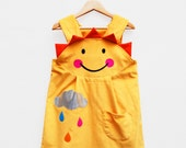 Girls pinafore dress with sunshine smiley face in yellow.