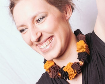 Felted necklace in mustard, brown and black with orange plastic beads