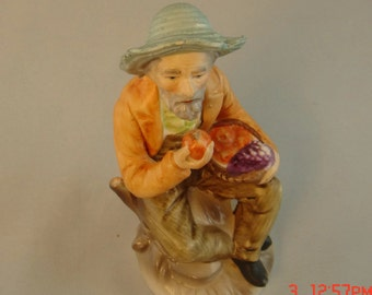Porcelain old man figurine, holding a basket of fruits, holding an apple. Hand painted and glazed.