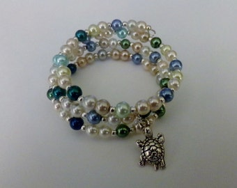 Under the sea memory wire bracelet with greens, blues and cream 6 mm pearls and silver tone turtle charm.  Delightful, with three coils.