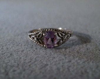 vintage sterling silver fashion ring with a large oval faceted amethyst stone and decorative floral setting, size 10    M