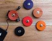 TunePoint, an earbud organizer / holder: vegetable-tanned leather, tan / orange / purple / black / maroon, minimalist, unique