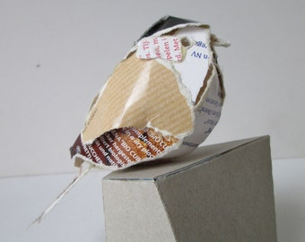 Small cardboard bird ( Willow tit) made of food packaging, sitting on a cardboard pedestal