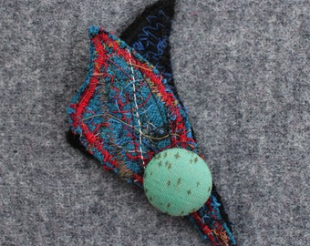 Wool textile art brooch with decorative covered button.