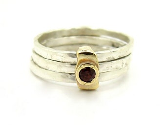 Stacking ring with a garnet set in gold and hammered silver bands