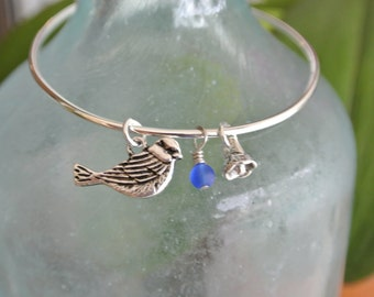 Spring is in the air!  A bird and flower charm on a silver bangle bracelet