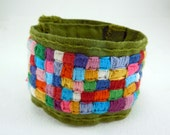 Rainbow Kiss cloth cuff bracelet, hand stitched patchwork design, multicolored squares on avocado green linen