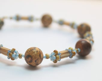 Hand beaded bracelet with 8mm antique agate in blue and brown with brass clasp