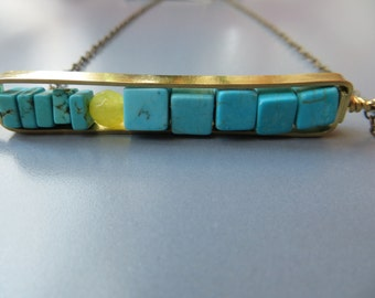 large brass horizontal frame with howlite and jade necklace