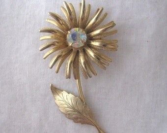 Gracious gold tone textured flower pin brooch with rhinestone center