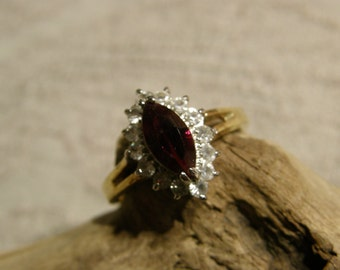 Vintage cocktail ring with a marquis cut red glass stone surrounded by rhinestones - marked BFL