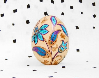 Floral pattern on brown chicken egg. Pysanka. Easter eggs.