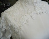 Lace bolero with Couture neck design, three quarter or full length sleeves, available in Ivory, White White or Black lace