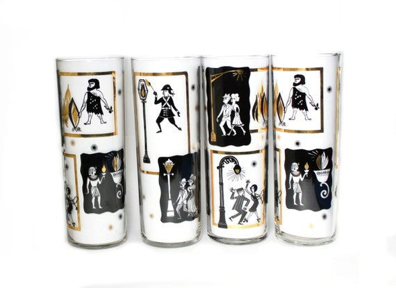 Bar ware. 4 black and gold high ball glasses. Images of historic people- caveman to the 1950's