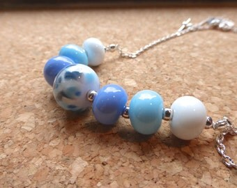 lampwork glass beaded necklace in white and blues with spots in purple, blue and grey