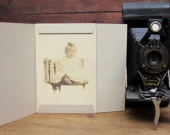 Antique Photograph of a Baby Dressed in White and Seated on a Victorian Era Chair with Sweet Little Face Sepia Tone Cabinet Card Portrait