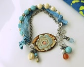 Pale blue, cream, and burnt orange bracelet w/ pottery cuff bead, sari silk, and silver ox chain