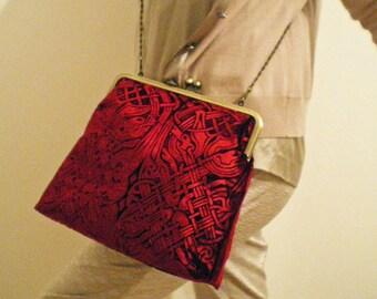 A beautiful kisslock handbag in an embossed iridescent velvet celtic design