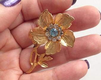 Flower brooch with blue crystal centre