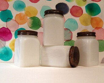 Beautiful set of four antique milkglass jars with tin lids. Great gift for the holiday's.