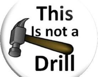 This is not a Drill. Item  FD26-01  - 1.25 inch Metal Pin back Button or Magnet