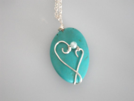 Wire wrapped turquoise bead pendant. Wrapped with silver plated copper wire & baby blue bead.