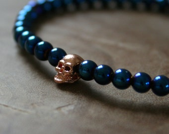 Blue Skull: an elastic beaded bracelet with rosegold skull and metallic blue dyed hematite beads.