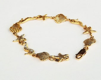 Bracelet With Sea Horses, Scallops, Starfish Ocean Theme Charms in Diamond Cut Gold
