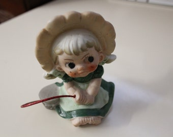 Vintage figurine of a upset little girl who hasn't caught a fish