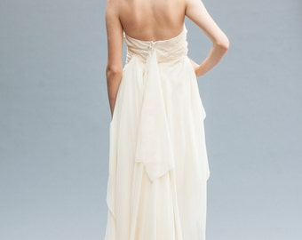 Short Wedding Dress. This backless wedding gown features luxurious Grecian draping in silk chiffon, ending in a floor length ruffled train.