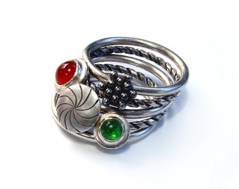 silver stacking rings, attached with four movable parts, green an red stones
