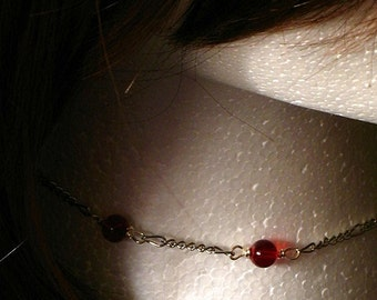 Vampire kiss choker necklace.  Silver chain, two red beads and skull dangler
