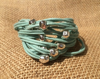 Cord bracelet, sterling silver pieces and metal clasp