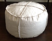Round pouf ottoman footstool in oatmeal colored canvas frayed edges