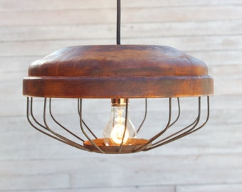 Hanging light from reclaimed chicken feeder brought back to life in rusted finish